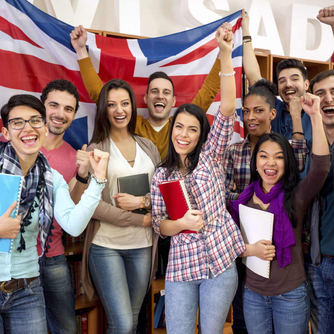 Cheerful British students with raised fists and flag of United Kingdom celebrate victory